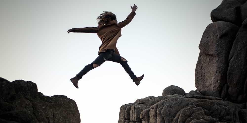 Une femme saute par-dessus un fossé