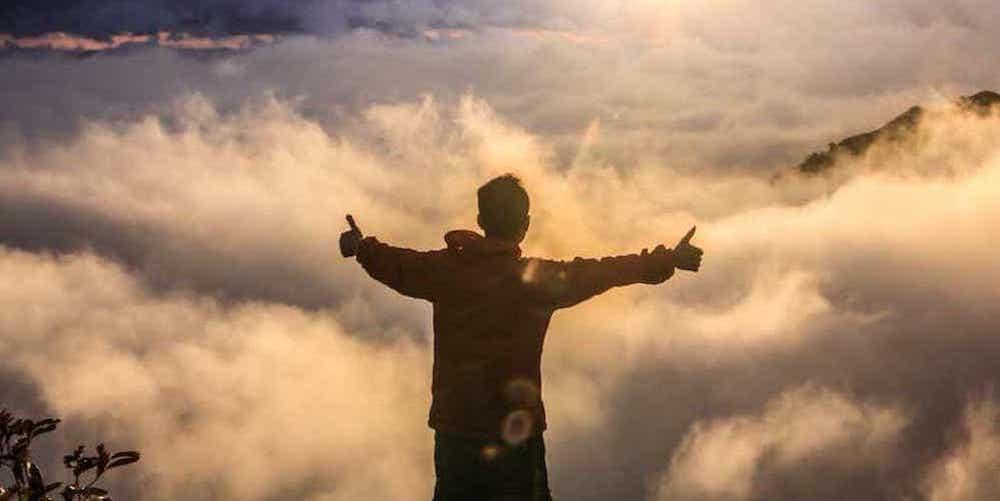 Un homme lève les pouces victorieusement au sommet d'une montagne
